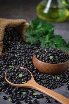 黒豆の袋は、暗いテーブルの上の木のスプーンで黒豆と豆をこぼします。