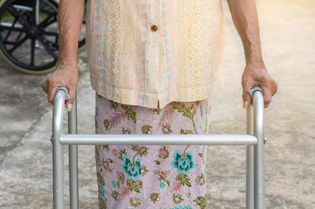Азиатская старуха, стоя с руками на трость
