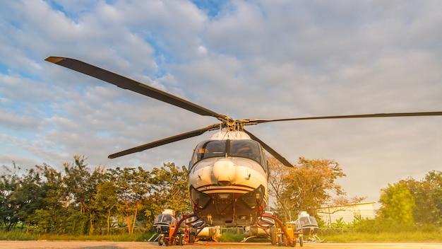 駐車場や滑走路で日の出の背景を持つメンテナンスを待っているヘリコプター