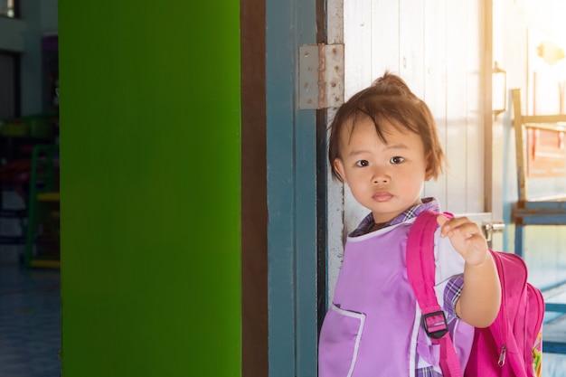 一般的な制服を着たアジアの就学前の小さな女子学生と学校に戻って学校に行く赤いバッグ。