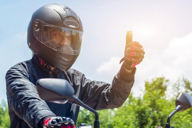 太陽光とオートバイのスロットル制御用のヘルメットと手袋を持つオートバイの男