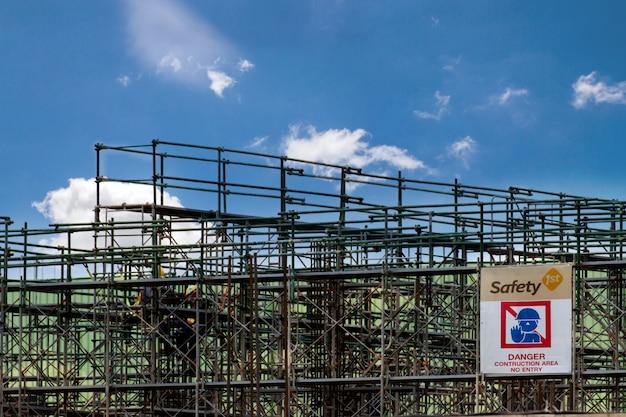 足場タワーと警告ラベルの建物、建設工場の足場のある建設現場
