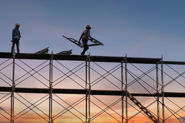 足場と建物、建設工場の足場と建設現場で作業する人