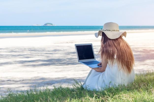 Молодая азиатская женщина используя компьтер-книжку в платье сидя на пляже, фрилансер девушки работая на море