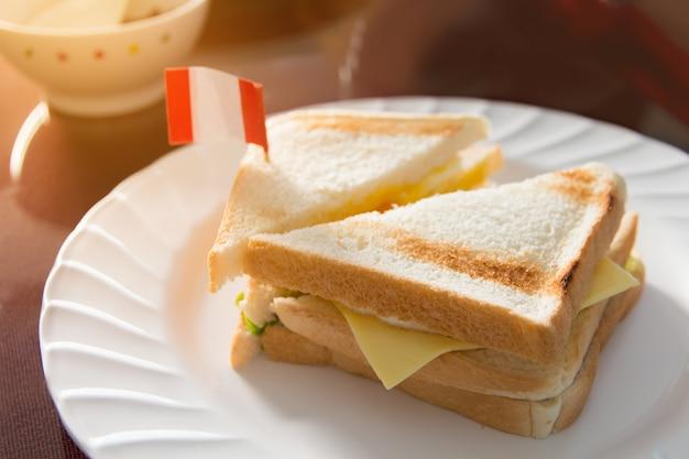 テクスチャと白い皿に新鮮なサンドイッチ、朝の皿にサンドイッチ