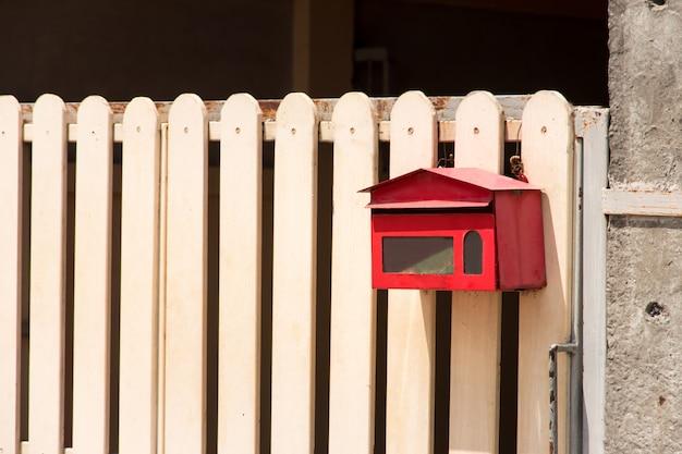 家と日光と美しい自然な背景のゲートの前のメールボックス