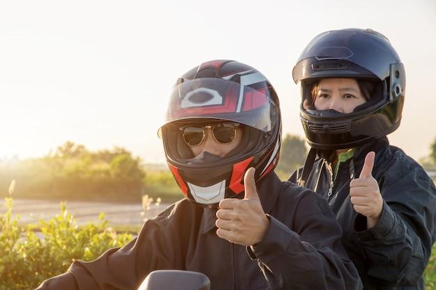 Азиатские мужчина и женщина с шлемом и носить и закрепить, прежде чем ехать большой мотоцикл велосипед на дороге для безопасности