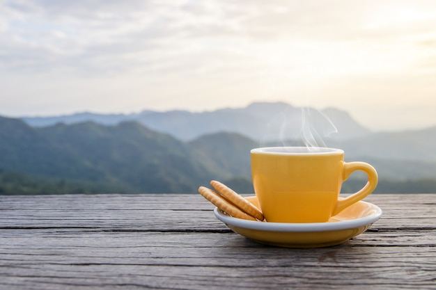 朝の霧と日光の背景、コーヒーの朝と山の木製の床にクッキーと一緒に置かれた熱いエスプレッソコーヒーマグカップの白いカップ
