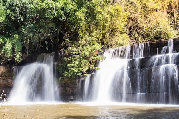 Живописная природа красивого водопада в бассейне пресной желтой воды озера в диком лесу, удивительное путешествие в таиланд и приключения