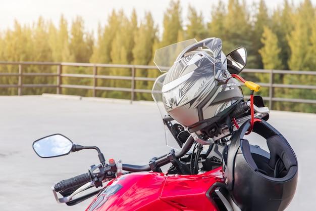 安全のためにスポーツバイクのフロントシートにぶら下がっているオートバイの手袋と安全ヘルメット