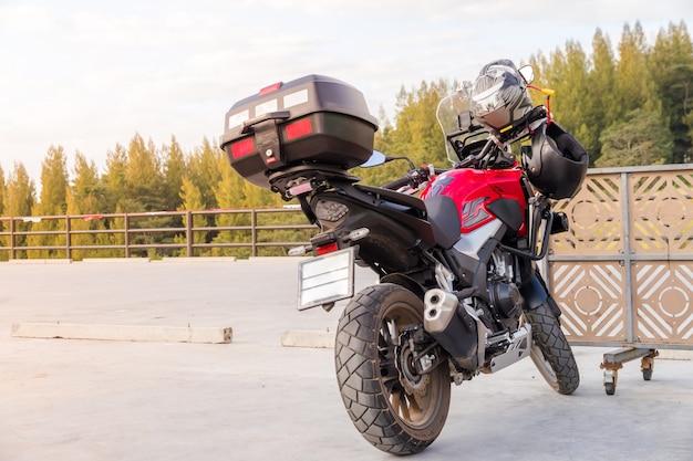 安全のためにスポーツバイクの前部座席にぶら下がっているオートバイの手袋と安全ヘルメット