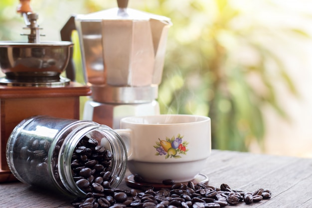 Чашка горячих кофейных кружек эспрессо и жареных кофейных зерен с горшком мока на деревянном полу