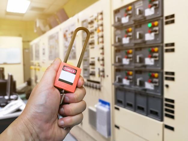 Рука, держащая красную кнопку блокировки и метку для процесса, отключенного электричества, переключить номер метки для электрического выхода из бирки