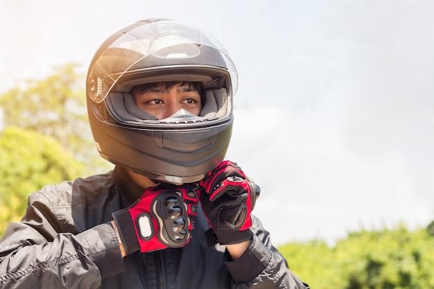 Человек в мотоцикле со шлемом и перчатками является важной защитой