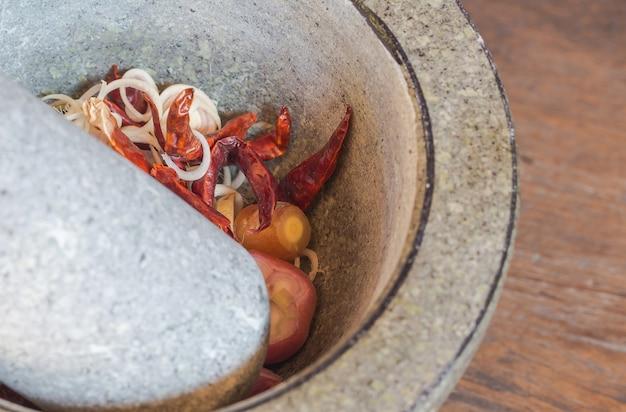 タイのスパイシースープの成分を乳鉢に、生の食材をカレーペーストに