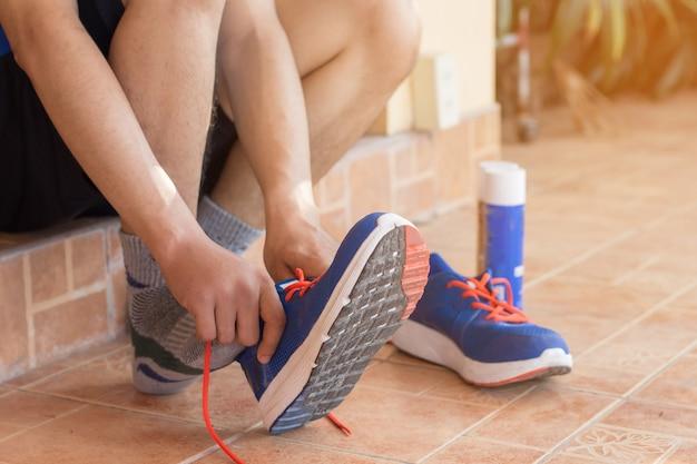 若い、アジア人、男性、ランニング、靴、前部、ジョギングの準備ができている男性ランナー