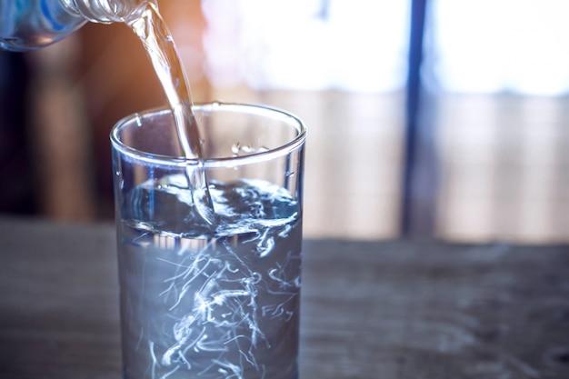 ガラスのテーブルの背景にボトルから精製された新鮮な飲み水を注ぐ