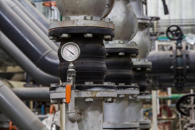工業用パイプと圧縮計量器、圧力計のクローズアップ