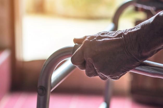 Азиатская старуха, стоя с руками на подножке