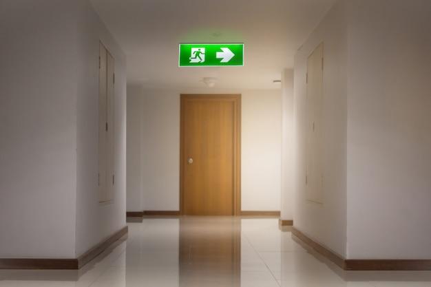 エスケープする方法を示すホテル内の緑の緊急出口標識