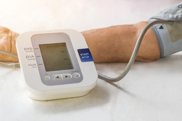 人々はデジタル圧力で血圧モニターと心拍モニターをチェックしています