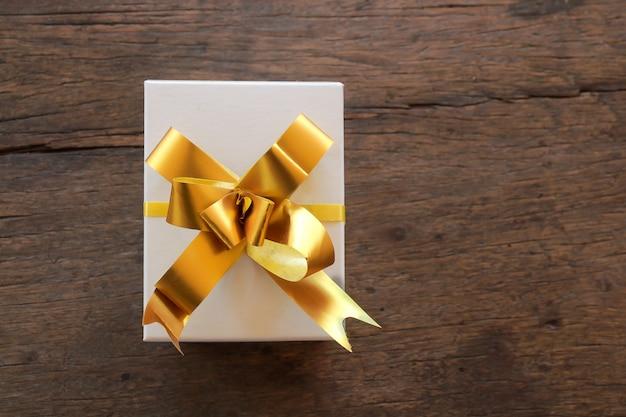 茶色の木製の背景、コピースペース平面図上のリボン付きギフトボックス