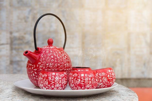ティーブレーキセット、木製のテーブルの上の熱いお茶の赤カップ