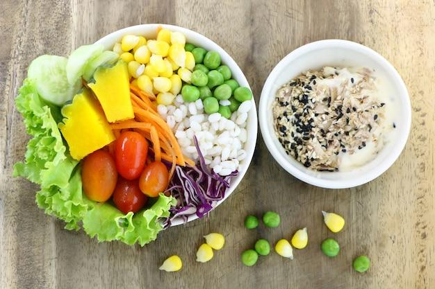 Здорового и диетического питания, салат из свежих овощей с салатом из тунца на деревянном столе