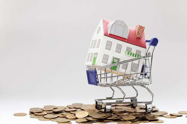 不動産投資の概念、家ミニチュアショッピングカートの机。