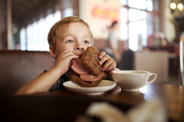 昼食中のカフェの小さな男の子。彼のサンドイッチからソーセージを食べる飢えた子供
