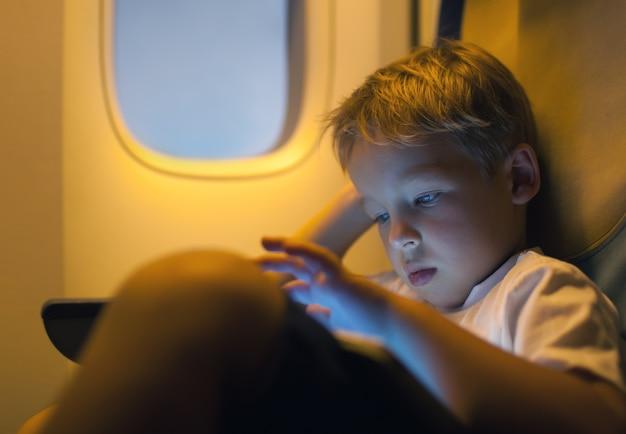 飛行中にタブレットコンピュータを使用して小さな男の子