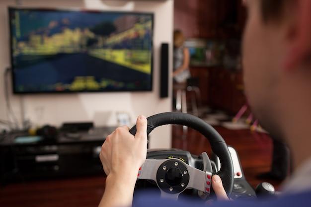 Человек, играющий в гоночную игру с симулятором рулевого колеса