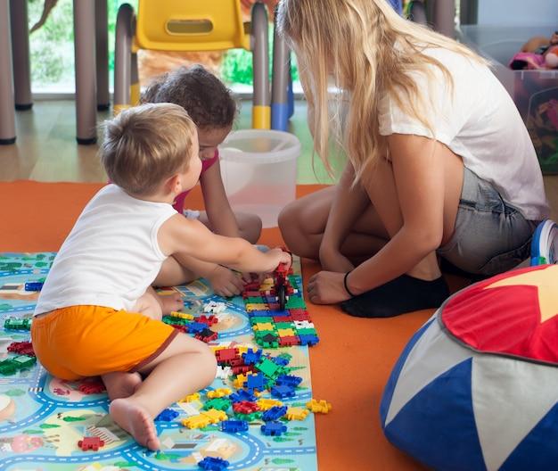 保育園で家庭教師とパズルをする
