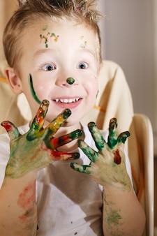 Симпатичный возбужденный мальчик с руками, полным краской пальца