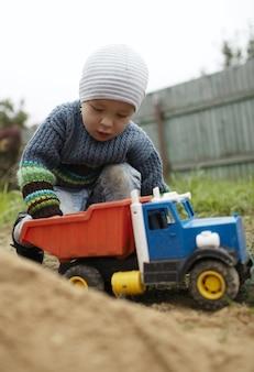 Мальчик играет с игрушечным грузовиком