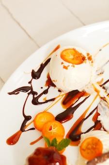 フルーツシロップとバターのキンカンのスライスとバニラアイスクリームのデザート