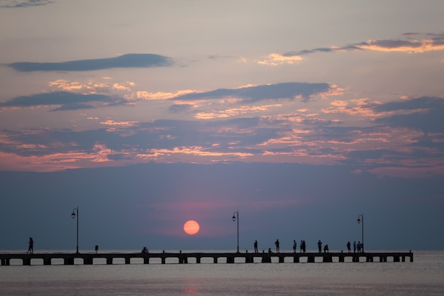街灯と歩いている人、日没に会う長い都市桟橋