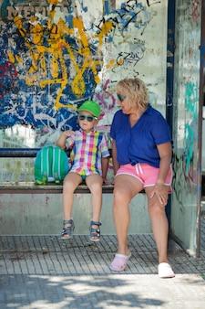 Бабушка и внук сидят на автобусной остановке