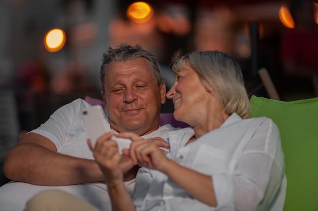 屋外でリラックスし、携帯電話の写真を通して見る陽気な成熟したカップル
