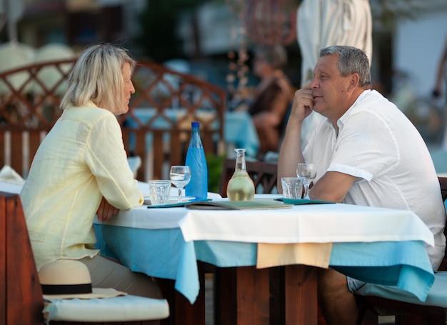 屋外カフェで夕食を食べて愛する成熟したカップル