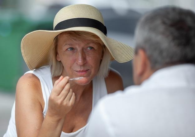 ストリートカフェで昼食をとりながら夫を見て夏帽子で成熟した金髪の女性