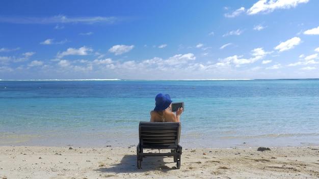 青い海の海岸で入浴パッド太陽を持つ女性