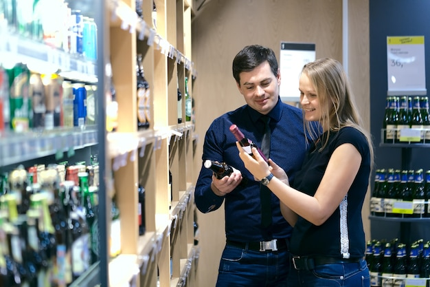 瓶の店でワインを選ぶカップル