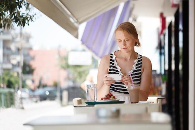 屋外のカフェで電話を持つ女性