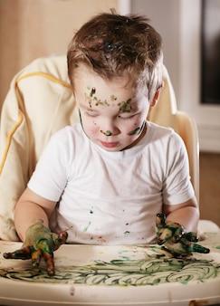 Творческий маленький мальчик, играющий с краской пальца