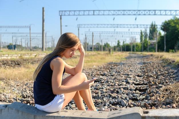 Девочка-подросток с мобильным сидением на незавершенной железнодорожной колеи