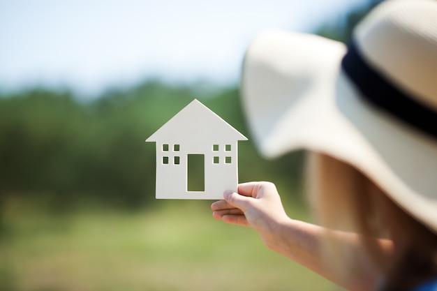 Женщина, держащая модель дома в сельской местности
