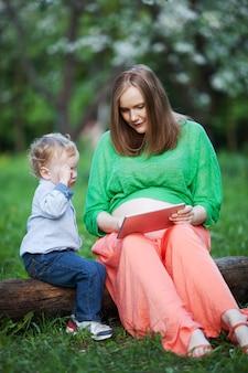 公園でタッチパッドを使用している小さな息子と妊娠した母親
