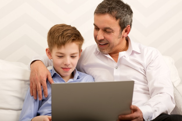 ラップトップを一緒に使っている少年と父