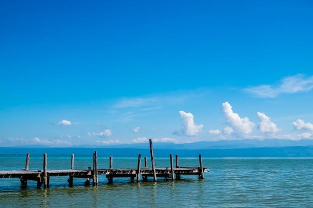 青い空と海の上の古い木製の桟橋